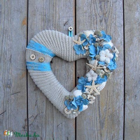 Egy vidám, tengerparti hangulatot idéző kopogtató, amit szívformára alkottam. Az alapot egyedi technikával készítettem, majd egy keményebb, vékony fonalból kötött anyaggal borítottam, ami így a nyári szalmakalap textúrájára emlékeztet. A szívforma jobb oldalát fehér kagylókkal, türkiz textil hortenziavirágokkal, saját készítésű horgolt virágokkal, izlandi zuzmóval, fa gombokkal és néhány terméssel dolgoztam el. Gyöngyökkel és tengeri csillagokkal díszítettem, majd a bal oldali ívre két…