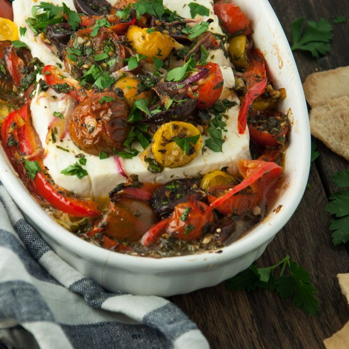 Mediterranean baked feta is roasted to perfection with fresh herbs, tomatoes, olives, and a drizzle of olive oil. This is an appetizer everyone loves! - Feasting Not Fasting