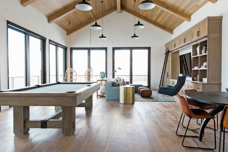 [Slide 6] A Brunswick pool table is the centerpiece of the bonus room, where chairs by Serena & Lily are suspended in a corner. The sofa is by RH, the lounge chair is by Room & Board, and the media center is by Acorn Woodworking.