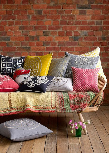 pillows & blanket on wood-frame couch.  ..........But where is the wood frame ?