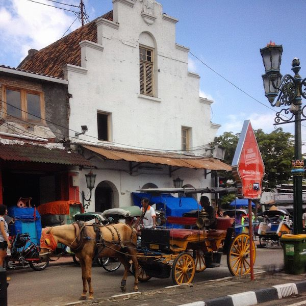 Yogjakarta's horse-drawn carriage in front of a Dutch colonial building