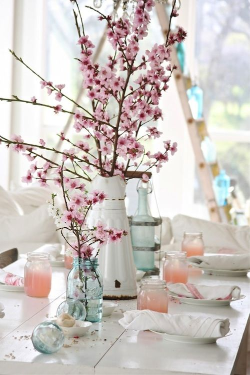 White and aqua vases with pink flower branches surrounded by Pink/peach candles on a white table with clean white plates.  Would be perfect to finish it off with some gold on the candle holders.