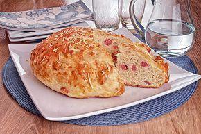 Pão de parmesão com linguiça com um pedaço cortado em um prato de servir branco.