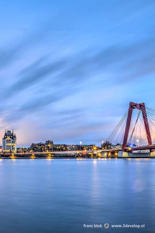Een zonsopkomst gezien vanaf het Noordereiland in Rotterdam. De lucht kleurt in een mooie mengeling van rood, paars en blauw.  Geheel rechts een van de rode pylonen van de Willemsbrug, opgeleverd in 1981.  Daarnaast twee bekende Rotterdamse gebouwen: het Potlood en het Witte Huis.  Op de voorgrond uiteraard het door de lange sluitertijd vervagende water van de Nieuwe Maas.
