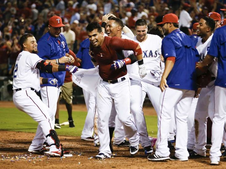 June 16: Texas Rangers catcher Robinson Chirinos (61) is congratulated by teammates as he arrives home on his walk-off home run against the Los Angeles Dodgers during the ninth inning of a baseball game at Globe Life Park in Arlington. The Rangers won 3-2.  -  © Jim Cowsert, USA TODAY Sports