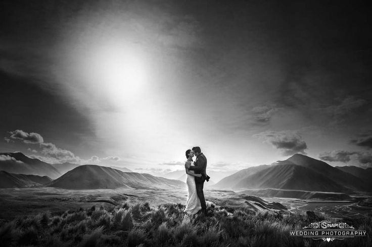 Dramatic black and white shot of a bride and groom framed by mountains.   More wedding photography by Anthony Turnham at www.snapweddingphotography.co.nz