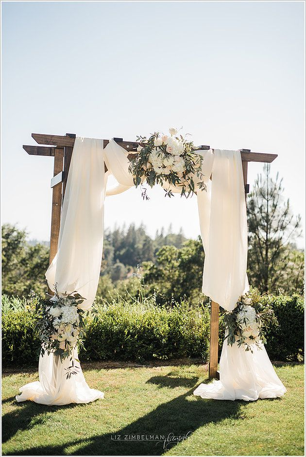 Romantic Wedding Flowers at Winchester Country Club | With breathtaking panoramic scenery and a championship golf course designed by Robert Trent Jones Sr. and Jr., it only made sense to frame the gorgeous view with a wooden arbor, draped with billowing white fabric, and adorned with large floral arrangements. | Visual Impact Design | Sacramento Wedding Flowers | Liz Zimbelman Photography