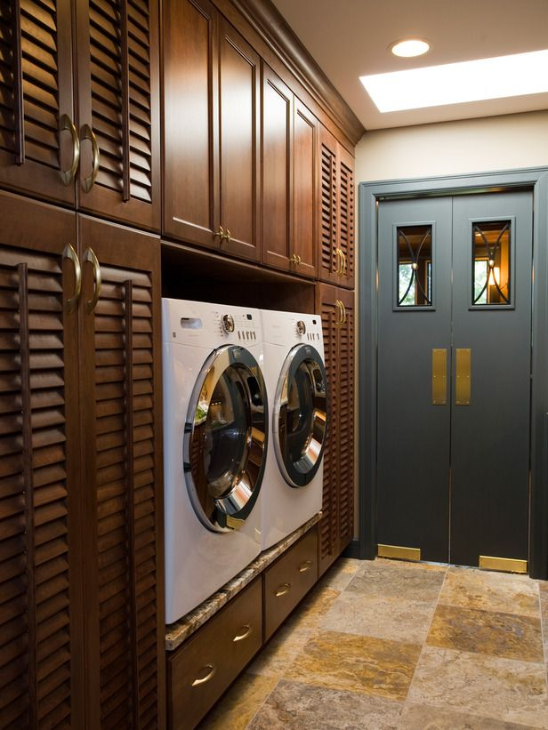 Designer Shane Inman takes advantage of floor-to-ceiling wall space with louvered cabinetry and pull-out drawers in this galley-style laundry room. Custom industrial-inspired butler doors take up minimal space and introduce an interesting design element into the space.