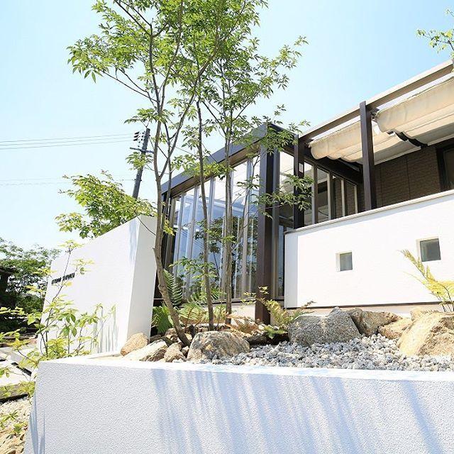 ガーデンルーム、ジーマの前に植栽を置くことで、くつろぎの空間を演出。 また、道路と宅地に大きな高低差があるため、腰壁を作り、室内にいる人の足元が見えないように配慮。