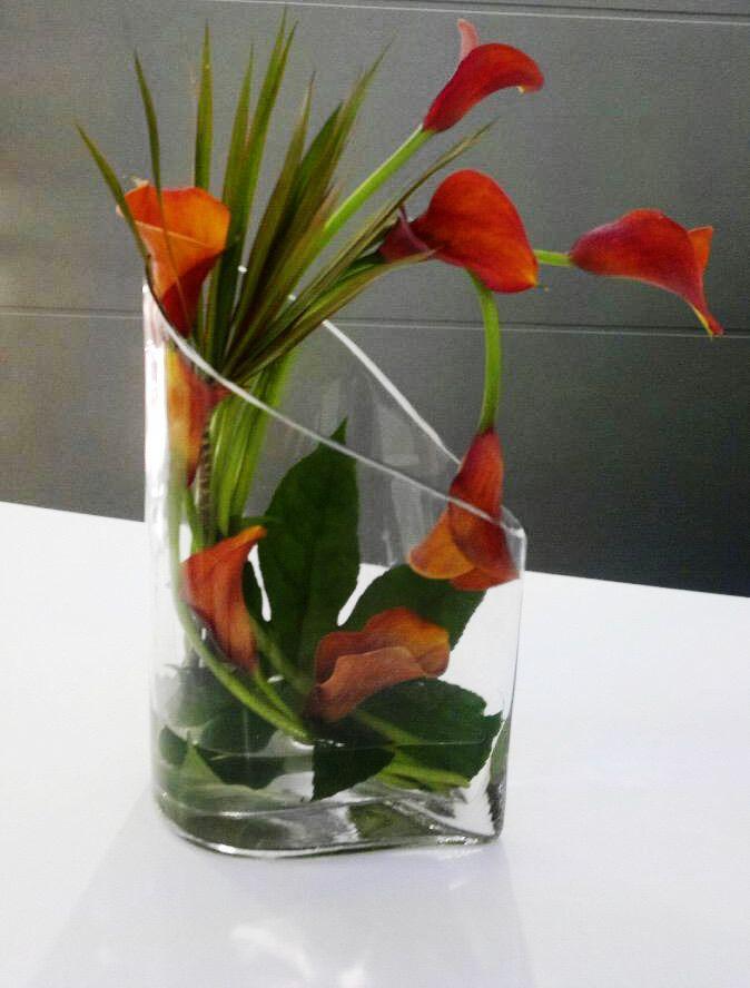 A very modern arrangement of 'Mango' Calla Lilies arranged into a unique clear glass vase