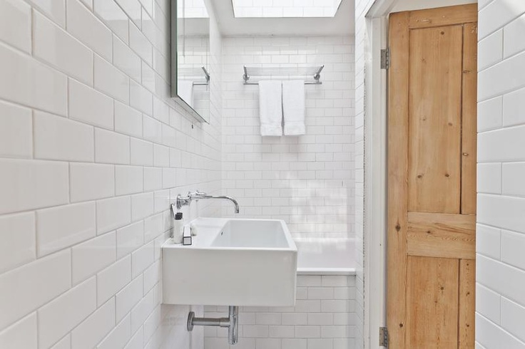 Full white subway tile bathroom with wooden door to shower