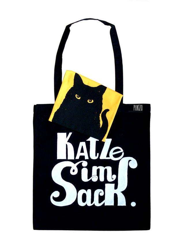 """Dieses Design wurde durch die Redewendung, """"Eine Katze im Sack kaufen"""", inspirert.    Der Schriftzug ist in weiß auf einer schwarzen Baumwolltasche gedruckt. Innen befindet sich ein..."""