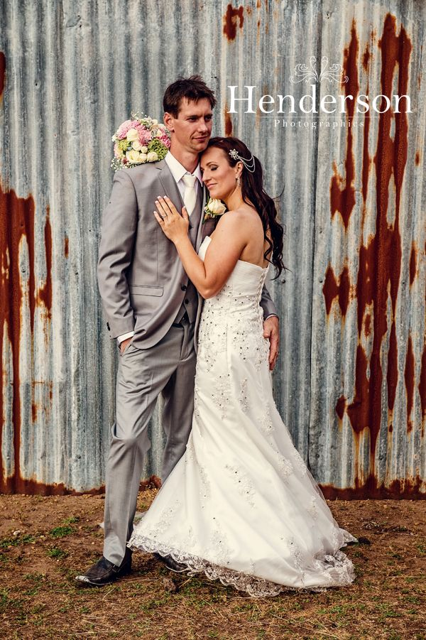 Bride and Groom snuggling against rusty corrogated iron. https://www.facebook.com/HendersonPhotographics