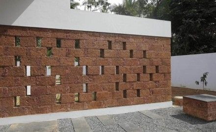 The wall is laterite, a building stone but per se not something with which the natural stone branch might occupy itself. t is a waste product of granite or basalt e.g. exposed to tropical climate for extended periods at the end of which often pronounced shades of red ensue. It is sometimes dense enough to use as a building stone but definitely easy to mine which is why it is the material of choice for low-cost building.
