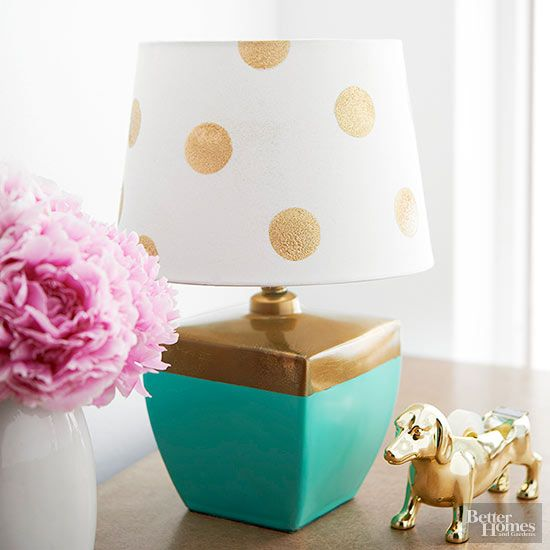 Brighten a ho-hum lamp with metallic accents. Tape around the cord and top of the lamp base with painters tape, then spray all-purpose primer and paint below the tape (we used aqua color paint). When dry, spray clear sealer over the paint, let dry and remove tape. Tape off the painted portion, and spray the top with gold metallic paint. For the shade, punch circles from cardstock to make a stencil. Press the stencil against the shade, spray with gold glitter, and let dry. Spray with clear…
