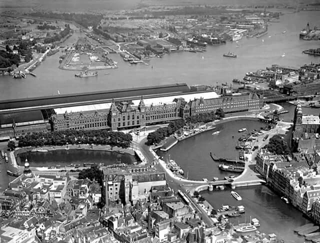 1950. Aerial view of the area around the Centraal Station. The latter is located in the center of the photo with the Stationsplein. At the top the river Het IJ. On the left the Open Havenfront. Photo Stadsarchief. #amsterdam #1950 #CentraalStation