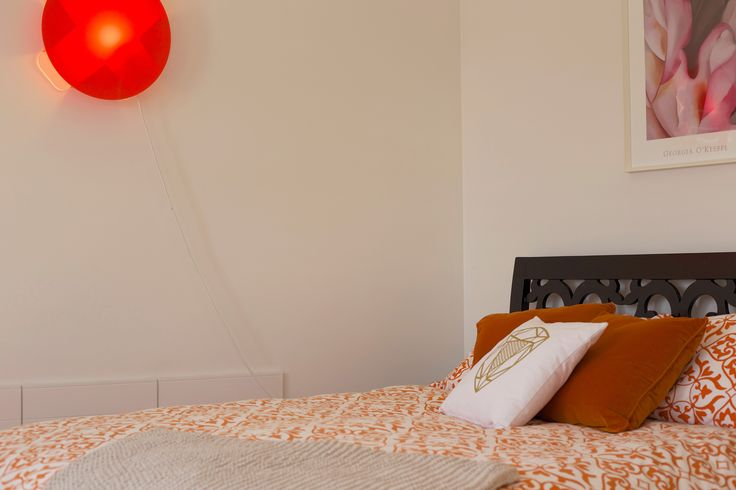 #catherine david light #orange light #orange bed linen. #lorna love cushion. Staging by Places and Graces.