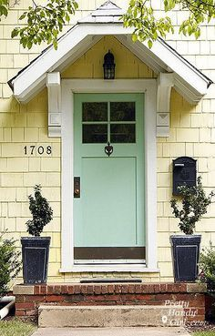A robins egg blue door on a yellow house gives instant coastal chic.