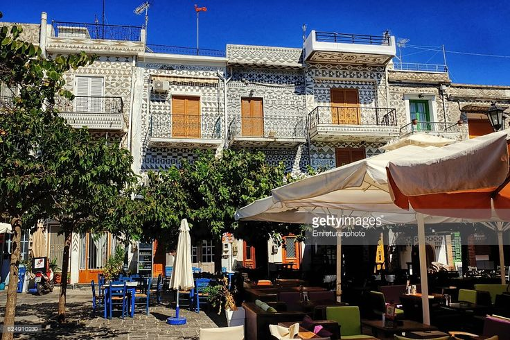 pyrgi is a famous village of chios island that is in unesco heritage list due to its geometrically designed building decorations as can bee seen in this Picture.this is section of town center-a small square with coffee shops and restaurants under sunshades.