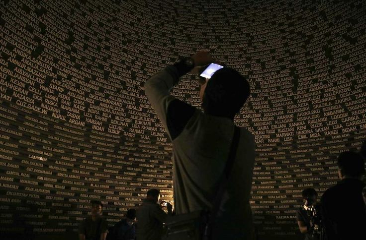Visitors take pictures of the glowing names of tsunami victims at Aceh Tsunami…