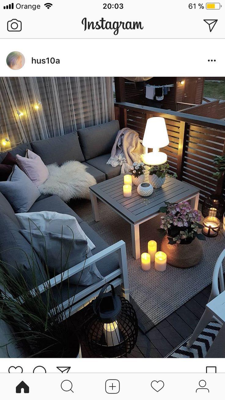 Kleiner Balkon mit gemütlicher Sitzecke, Kerzen und Laternen. – lamodademama