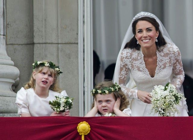 Lady Louise Windsor (L) Lady Grace van Cutsen (ears covered) and Kate on the balcony of Buckingham Palace.
