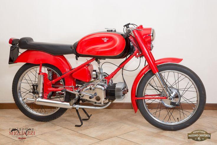 MOTO RUMI SUPER SPORT Nazione: Italia Tipologia: Sport Anno: 1956/1957 Tipo di motore: Bicilindrico a 2 tempi Cilindrata: 124,68 cc Potenza: 7 CV  Cambio: 4 marce Velocità massima: 100 Km/h Colore: Rosso con fascia nera sul serbatoio (maggiorato)