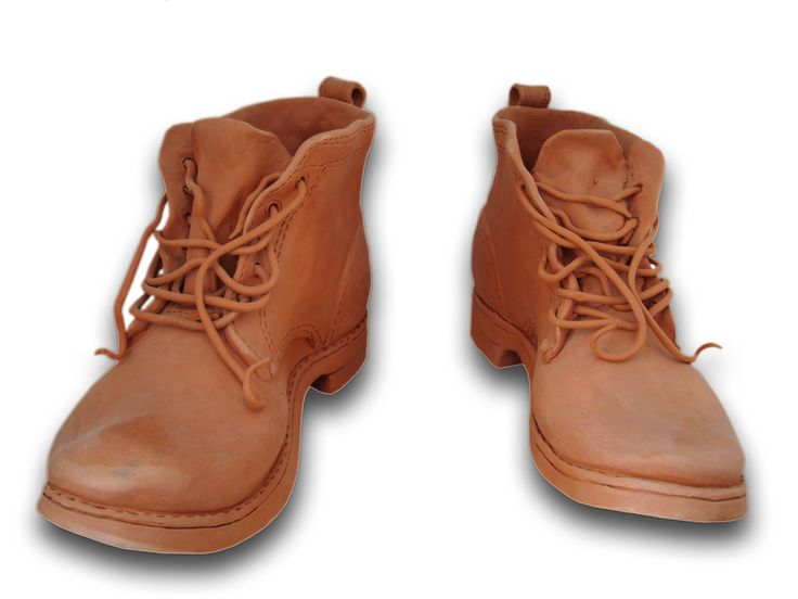 """""""Boots"""" is a work of handmade ceramic art presented by George Atsonios at the Pan-Hellenic Ceramics Exhibition in 1982.  """"Boots"""" was the first-prize winner amongst works of numerous pottery artists of Maroussi, which is also where the Sifnian artist permanently resides."""