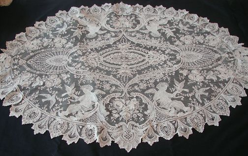 Exquisite Brussels Point De Gaze Lace w/ Cherubs A rare and wonderful oval table center of Brussels Point De Gaze lace. A superb design with large ornate cherubs and doves, meandering vines and large three-dimensional roses. A gorgeous piece for the Brussels lace collector, superior in design and workmanship.