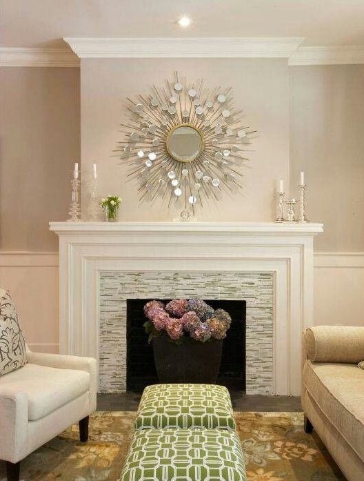 Gorgeous mantel decorating. White painted wood mantel with dimensional tiers built in. White and gray horizontal stone tile. Gold mod circles mirror paired with glass candlesticks.