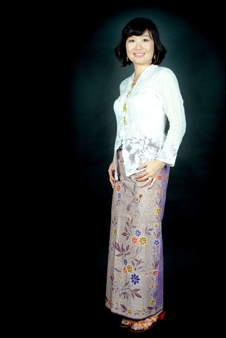 Little Nyonya Della in white embroidered kebaya and full hand drawn batik (batik tulis) sarong light brown-purple