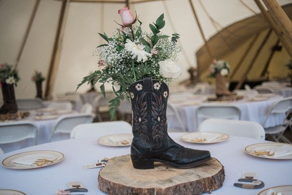 Rustic wedding centerpiece idea - western-inspired centerpiece with cowboy boot filled with daisies, roses and greenery on tree slice {A+P Photography}