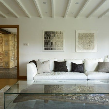 An old threshing table has been encased in sleek glass and re-purposed as a coffee table. Design by Pippa Paton Design