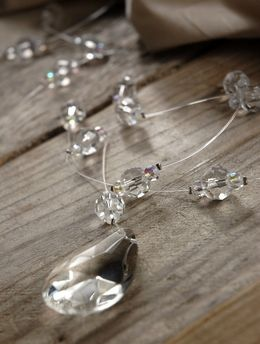 6.50 SALE PRICE! Measuring 6 feet, this acrylic crystal garland features a large weighted almond cut crystal at its base. Strung along the clear plastic fila...