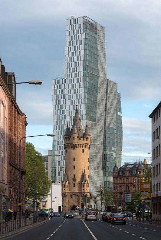 En el primer plano esta Eschenheimer Turm, el edificio más antiguo y sin alteraciones en el distrito Innenstadt (centro de la ciudad) de Frankfurt, Alemania. Erigido a comienzo del siglo 15 (1426-1428), la torre era una entrada de la ciudad que formaba parte de las fortificaciones de la Edad Media tardía de Frankfurt. Elevándose por encima y detrás de la torre de 47 metros (154 pies) esta Nextower, un alto edificio de oficinas de 136 metros (446 pies) terminado en 2009.