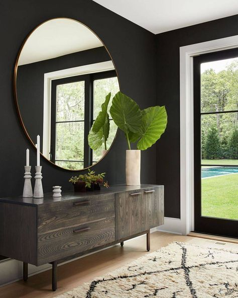 round mirror over console in entryway with black walls