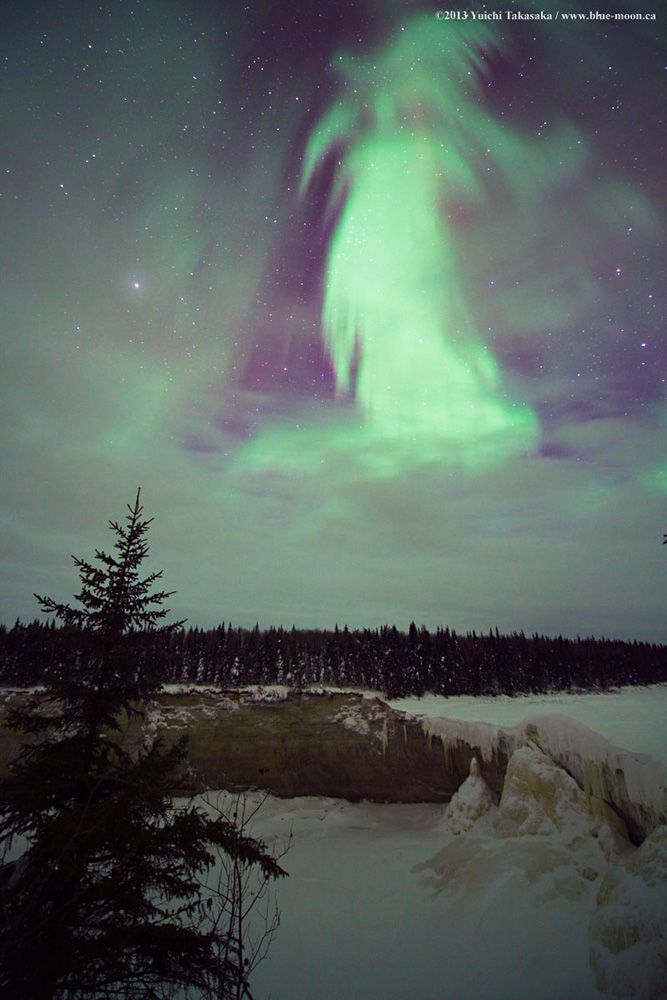 Through a window in the clouds aurora Borealis (the Northern Lights) appear in a spooky form over winter landscape of northern Canada. Yuichi Takasaka