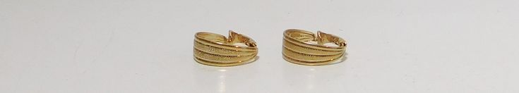 Wedge shaped small gold tone clip on earrings with a brushed metal design. Signed LH Segal California.