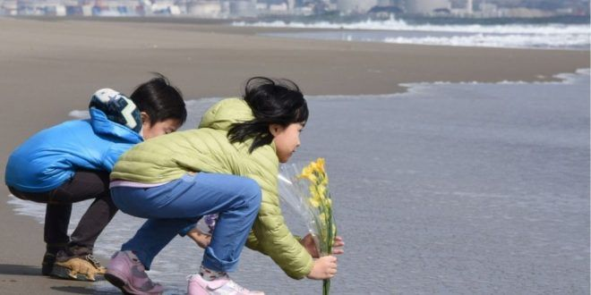 Non loin de la centrale nucléaire de Sendai, des enfants rendent hommage aux victimes du 11 mars 2011 en envoyant des fleurs dans l'eau