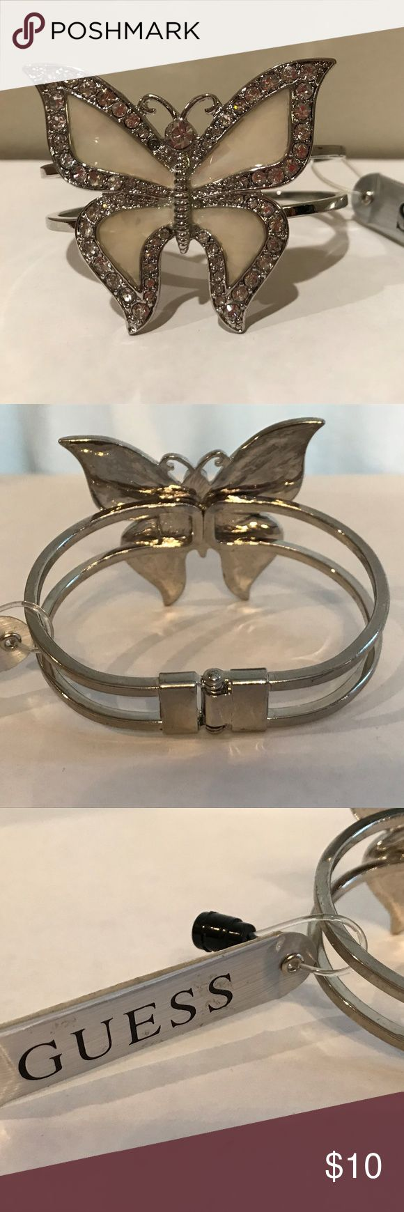 "Guess Butterfly Hinged Bangle with Crystals A beautiful butterfly hinged bangle of cream mother-of-pearl-look body outlined in crystals. It still has the Guess tag attached but unfortunately it is missing a small crystal at the top left of it's head. I didn't notice the missing crystal until I took the main picture. The butterfly measures 1-3/4""h x 2""w. Guess Jewelry Bracelets"