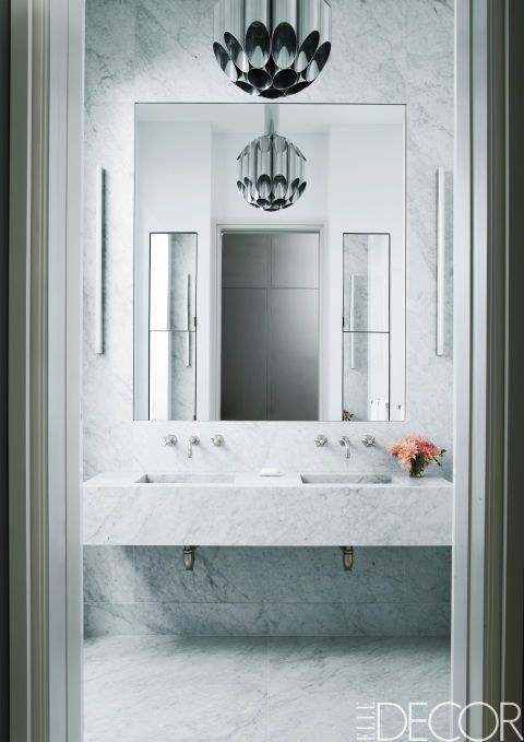 A large, frameless mirror complements the crisp aesthetic of this marble master bathroom of a SoHo loft. A 1960s FontanaArte light fixture hangs above a cantilevered Carrara marble sink.  Get the look: Frameless Rectangular Mirror, $230, lampsplus.com