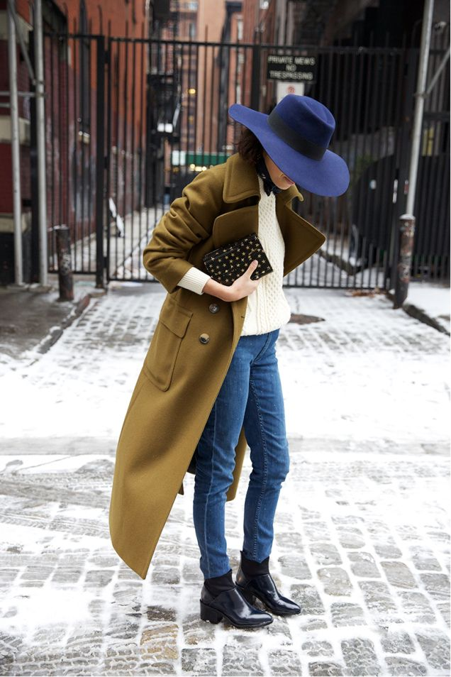 olive coat with a navy hat and tapered jeans