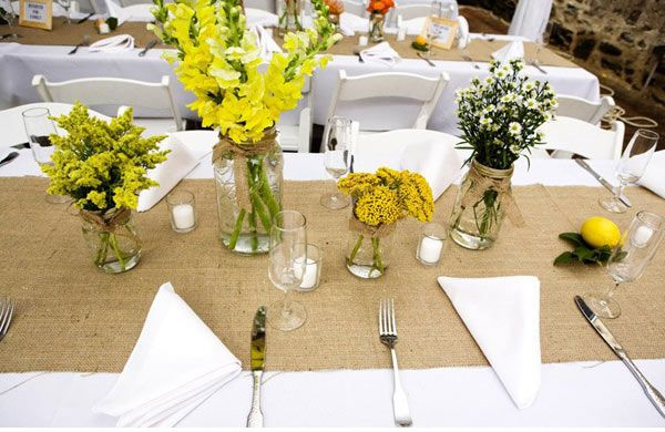 burlap over plain white table covering & assorted flowers in mason jars