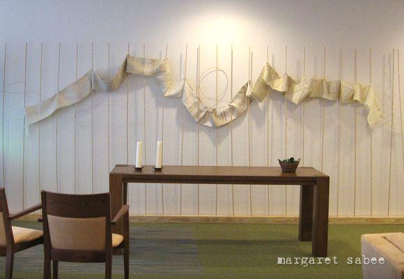 Dit is een wandobject in een bezinningsruimte van een verpleeghuis. De stokken vertegenwoordigen de kosmische verbondenheid en het weefsel de levensfasen van de mens (lees: levensweg). In het weefsel zijn biografische elementen op eenvoudige manier ingeweven of uitgedrukt via materiaal en technieken.  Materiaal   Wol, katoen, linnen, pitriet, hout en fantasiedraden  Levertijd     Prijs     Prijs is afhankelijk van