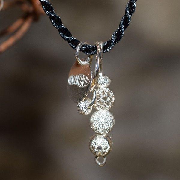 NA JEHLE- Náhrdelník navlečen na pevné černé hedvábné 2 mm silné šňůře,ozdoben stříbrnými perlami na jehle, stříbrným kroužkem s komponentem a medailonkem Impronte .Délka až 44 cm, přetahování přes hlavu. Stříbro Ag 925.