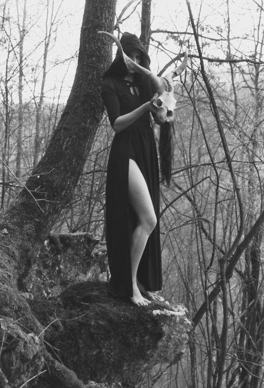 Mór-ríoghain - Laura P. Witch. Bruja con craneo de animal con cuernos en las manos. Capucha en el bosque