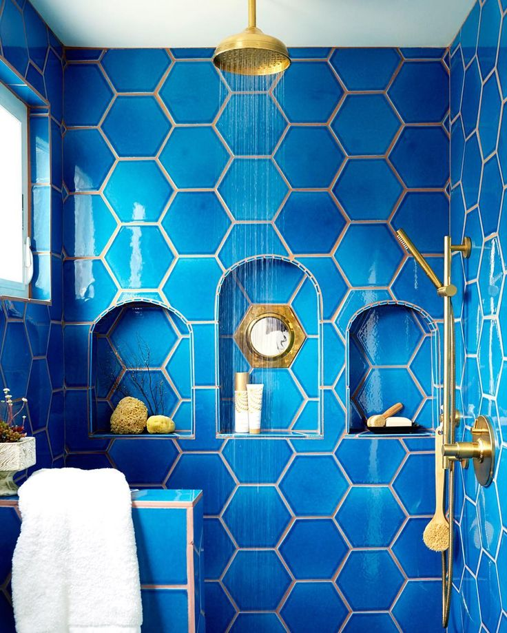 Gorgeous blue large scale hex shower tile with niches and brass hardware.  Justina Blakeney