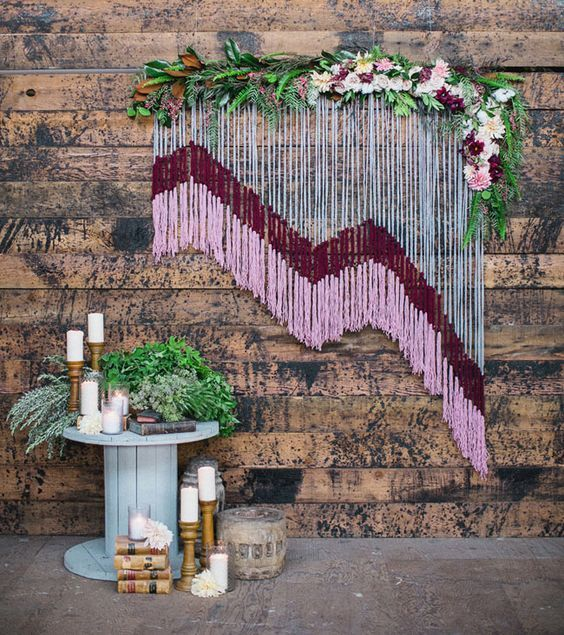 yarn wedding backdrop with floral accents / http://www.deerpearlflowers.com/boho-macrame-knotted-wedding-decor-ideas/