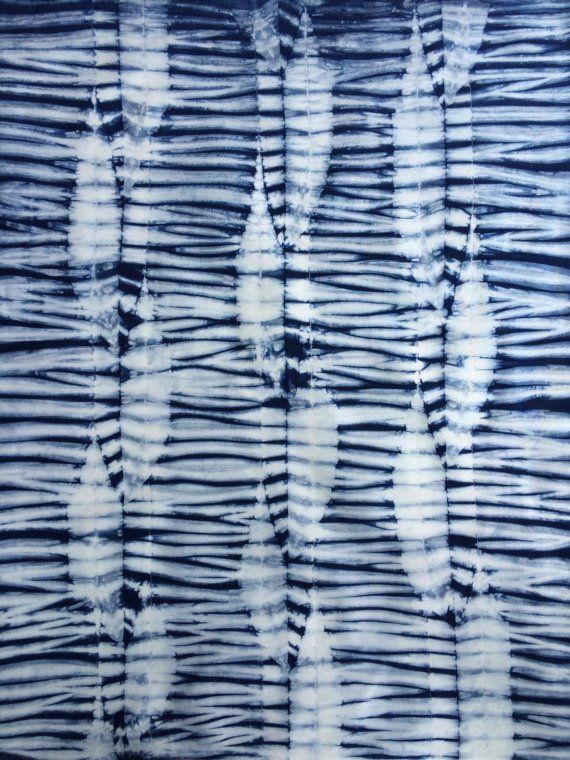 Questo tessuto indigo ha colonne del set di foglia, o forme piumate, contro un terreno spogliato blu e bianco. Fu creato nella tecnica giapponese Shibori resistere e tinto ripetutamente in indaco per ottenere una tonalità di indaco medio-scuro. Terra bianca pulita fornisce il contrasto e il bilanciamento chiaro/scuro. Le foto qui sono un composto di parecchi quarti grassi con questo disegno. Riceverai uno simile. Io uso il cotone di Robert Kaufman Kona di qualità superiore che è un cot...