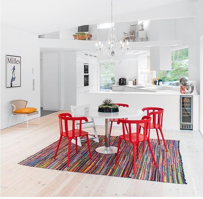 Białe wnętrze domu plakat we wnętrzu czerwone kolorowe krzesła okrągły stół na jednej